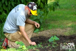Another volunteer, Kyle, works to plant inside the garden.